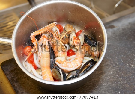 Seafood soup cooking in metal pot on commercial kitchen, copy space