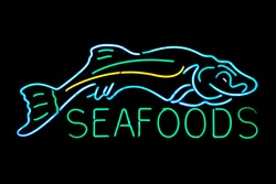 Seafood with fish neon sign isolated on black background