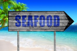 Seafood wooden sign with a beach on background