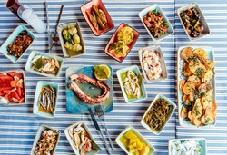 Seafoods, grilled meat, meze, herbs, fish, raki, ouzo, appetizers and salads in Greek or Turkish Fish Restaurant on the table for dinner or lunch at the beach from Greece or Turkey.