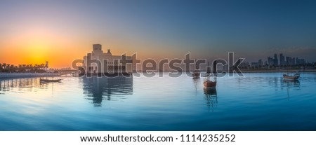 Seafront of Doha park and East Mound-Skyline view during purple sunset with boats, Qatar. #1114235252