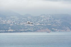Seagull flies over the Mediterranean Sea on a foggy day, in the background out of focus you can see the houses on the mountain and the coastline.