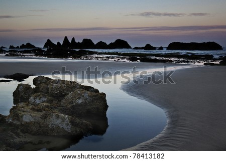 Seal Beach sea stacks along the Oregon coast beyond the beach at sunrise