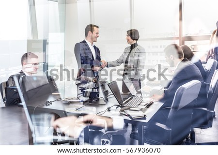 Sealing a deal. Business people shaking hands, finishing up meeting in corporate office. Businessmen working on laptop seen in glass reflection. Business and entrepreneurship concept. #567936070