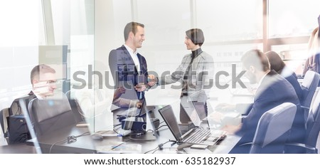 Sealing a deal. Business people shaking hands, finishing up meeting in corporate office. Businessmen working on laptop seen in glass reflection. Business and entrepreneurship concept. #635182937