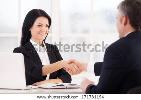 Sealing a deal. Two cheerful business people handshaking and smiling while sitting face to face at the table
