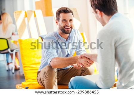 Sealing a deal! Two happy young men shaking hands while sitting in the rest area of the office