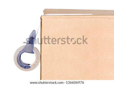Sealing tape and box. Blue adhesive tape roll dispenser sealing a brown cardboard box. Profile, side view. Isolated on a white background. Copy space, room for text.