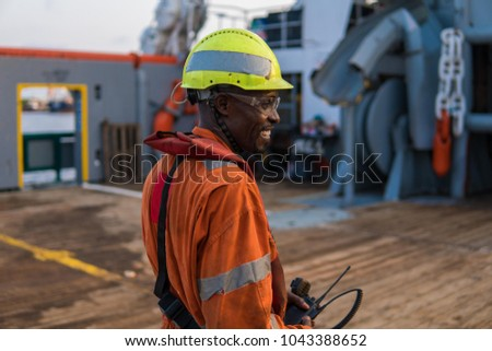 Seaman AB or Bosun on deck of offshore vessel or ship , wearing PPE personal protective equipment - helmet, coverall, lifejacket, goggles. He holds VHF walkie-talkie radio in hands.