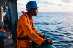 Seaman AB or Bosun on deck of vessel or ship , wearing PPE personal protective equipment - helmet, coverall, lifejacket, goggles. Safety at sea