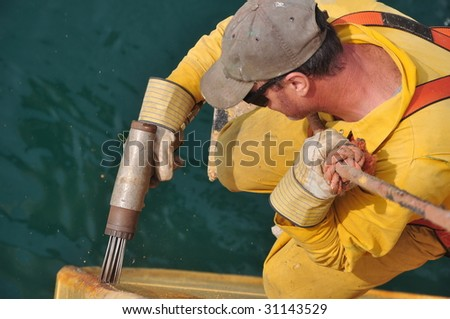 seaman removes rust from ship's hull