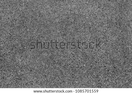 Seamless asphalt road background. Grainy texture with gravel particles, small stones, black, gray and white grains. Close up, top view.
