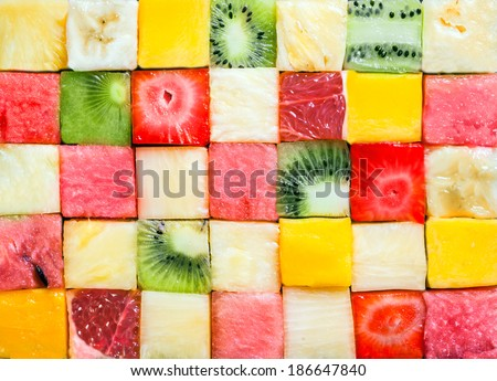 Seamless background pattern and texture of colourful fresh diced tropical fruit cubes arranged in a geometric pattern with melon, watermelon, banana, pineapple, strawberry, kiwifruit and grapefruit - stock photo