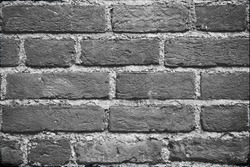 Seamless dark grey brick wall texture background. Pattern of weathered old cracked brickwall. Stacked stones wall. Home or office design backdrop. Brick work wall from old building architecture.