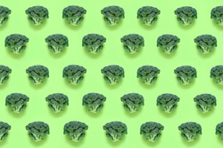 Seamless minimalistic pattern with broccoli on a green background. Photo collage, vegan pop art design, vegetable backdrop, diet, healthy food. Postcard, print on fabric, wrapping paper. Top view.