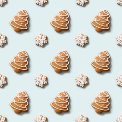 Seamless pattern of decorative cookies in shape of snowflakes and Christmas tree on blue background. Xmas holiday abstract background.
