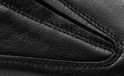 Seams on the leather of shoes. Close up.