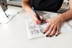 Seamstress creates a sketch in the working notebook. designer draws the clothes and bags.