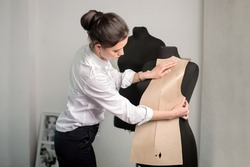seamstress designer applies pattern template at mannequin at seamstress studio