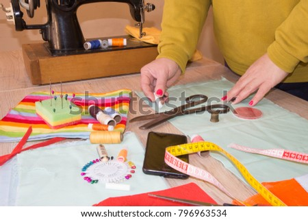 Seamstress hands on the work table with measuring tape. Tailor hands working with scissor and suit textile cloth. Fashion Designer Cutting Fabric In Studio #796963534