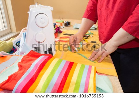 Seamstress hands on the work table with pattern and measuring tape. A tailor is laying out a dress. Sewing layout #1016755153