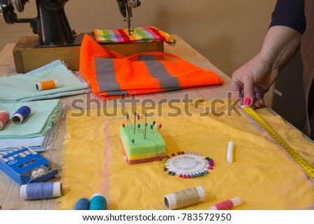 Seamstress hands on the work table with pattern and measuring tape. A tailor is laying out a dress. Sewing layout #783572950