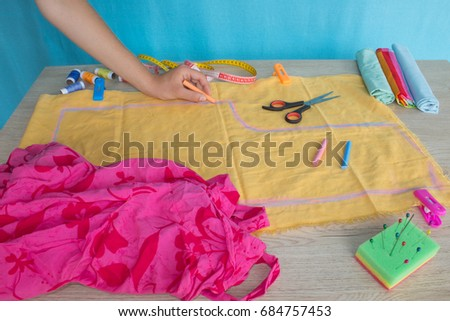 Seamstress hands on the work table with pattern and measuring tape. Tailor hands working with scissor and suit textile cloth #684757453