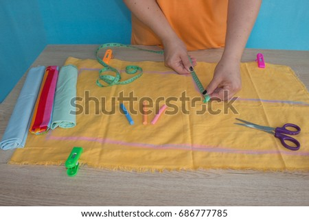 Seamstress hands on the work table with pattern and measuring tape. Tailor hands working with scissor and suit textile cloth #686777785
