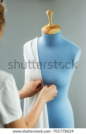 Seamstress measuring beautiful fabric on blue tailor dummy in her workshop. #705778624