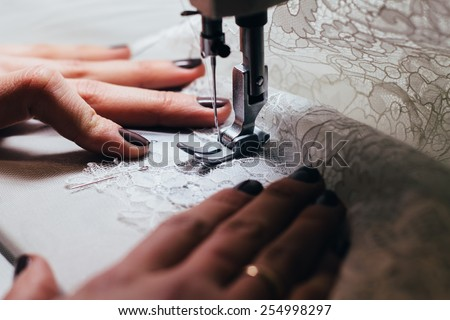 Seamstress , sewing lace wedding dress on the sewing machine .