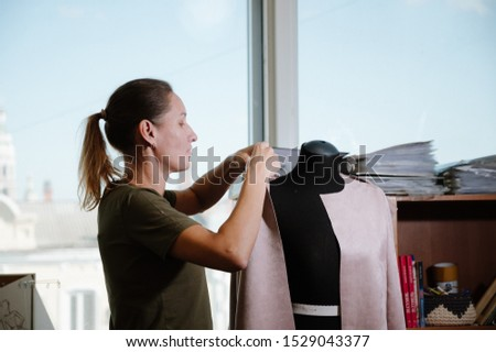 seamstress standing near mannequin and hanging up cloth in sewing studio.Creation or modelling of fashion clothes. Designer clothes concept