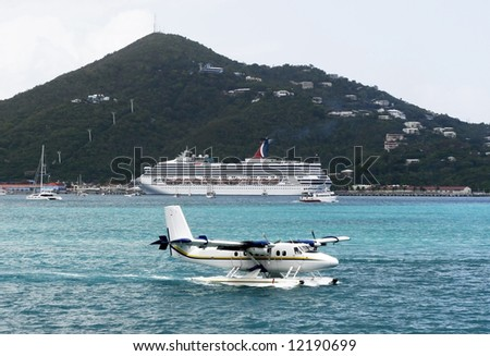 seaplane landing with cruise ship in background