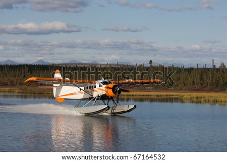 Seaplane makes a landing on a calm Alaskan lake. - stock photo