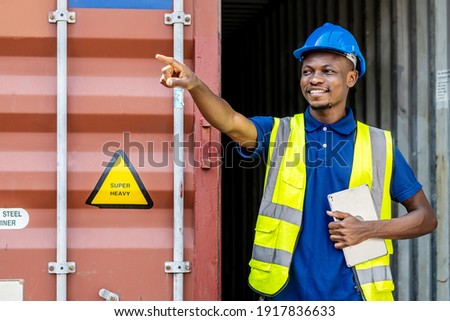 Seaport inspector busy with in-checking on cargo and pointing to position loading Containers box from Cargo freight ship at Cargo container shipping on a large commercial shipping dock Zdjęcia stock ©