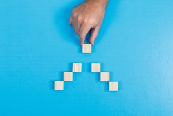 Search and ranking concept with wooden cubes on cyan blue background top view. man holding the separated cube at the top.