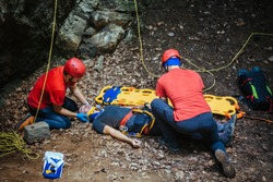 Search and rescue team helping injured alpinist