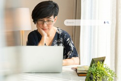 Search Engine Optimization - SEO concept. Portrait of a beautiful middle-aged asian woman using laptop computer a on the table. Machine learning, AI Artificial intelligence, Keyword, Lifestyle.