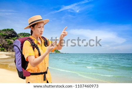 Search for apps and Navigation concept. Asian woman traveling backpacker hiker use smart phone and touching a mobile screen on the beach . #1107460973
