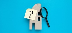 Search for hidden defects in real estate. Miniature house and question.