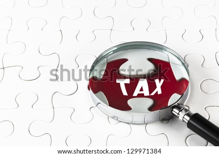 "Search for missing puzzle pieces ""TAX"" with a magnifying glass - stock photo"