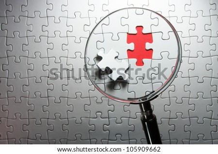 Search for missing puzzle pieces with a magnifying glass. Concept image of detecting a defect.