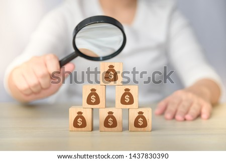 search for money. hand holding magnifying glass investigating wooden block with money bag icons.  money management concept. passive income. money saving concept. Foto stock ©