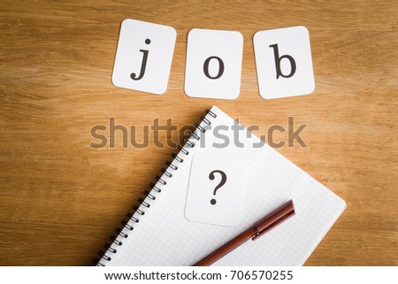 Search or choose a job.  Looking for a dream job. Career concept. Inscription job on the wooden table and sign of question on the notebook. #706570255