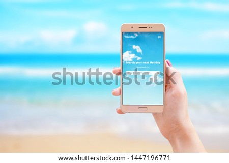 Search your next holiday travel app on smart phone in woman hand. The concept of using the internet and apps for finding destinations and booking tickets and accommodation. #1447196771