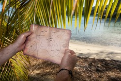 Searching for a buried treasure with a map on a deserted tropica