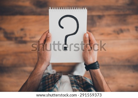 Searching for answers. Top view of man holding note pad with question mark on it while standing on the wooden floor
