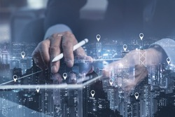 Searching location on map pin above city scape, network connection technology, internet of things, satellite navigation system concept. Double exposure of man using digital tablet and smart city