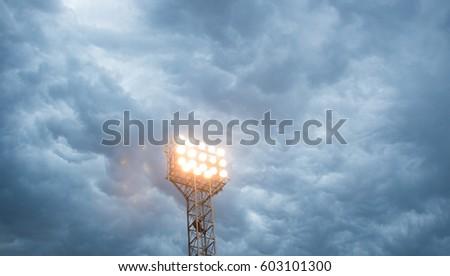 Searchlight tower on a dark sky background. Mast with spotlights illuminate on stadium and night sky background