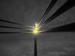 Searchlights on the bridge. Portable LED light tower. St. Irenaeus Pedestrian Bridge over the Sava River, Sremska Mitrovica, Serbia. Evening sky with clouds. Metal pillars and beams. Yellow light