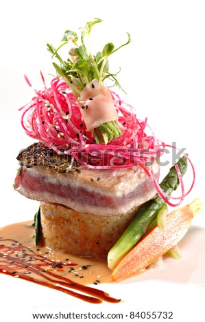 Seared ahi tuna, beet slaw & ginger wrapped sprouts served over rice with a ginger sauce on a white plate